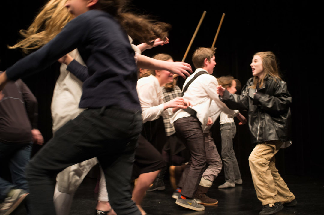 middle school actors perform stage combat on stage for theatre class