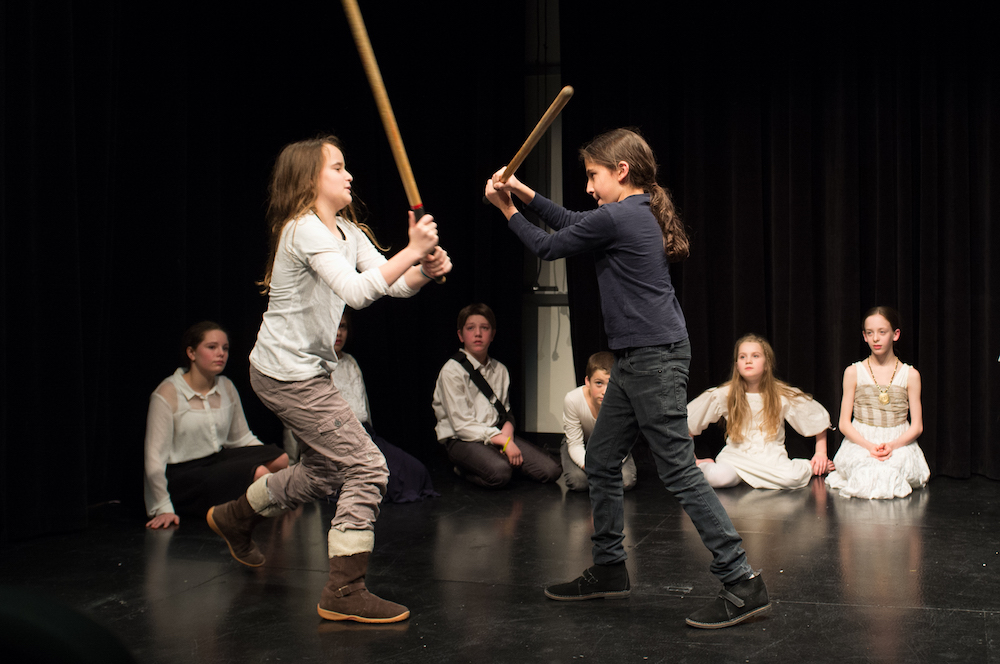 middle school and high school rehearsing stage combat at theatre class