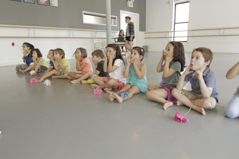 10 children stretching faces in theater class